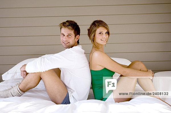 Porträt eines Paares  das Rücken an Rücken auf dem Bett sitzt.
