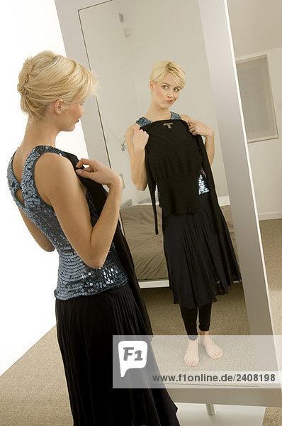 Junge Frau beim Anprobieren eines Kleides vor dem Spiegel