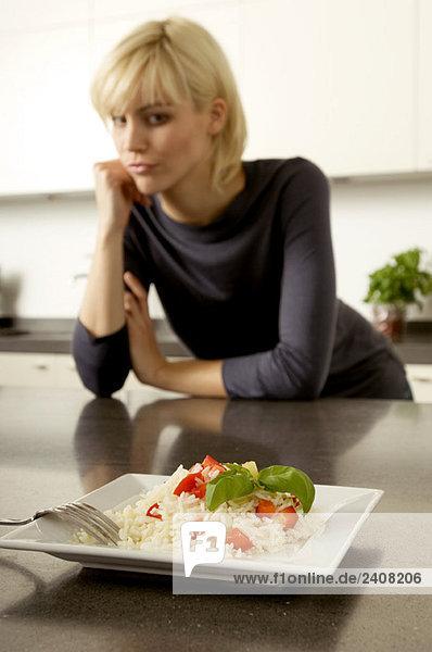 Teller mit Reis vor einer jungen Frau  die sich gegen eine Küchenzeile lehnt.