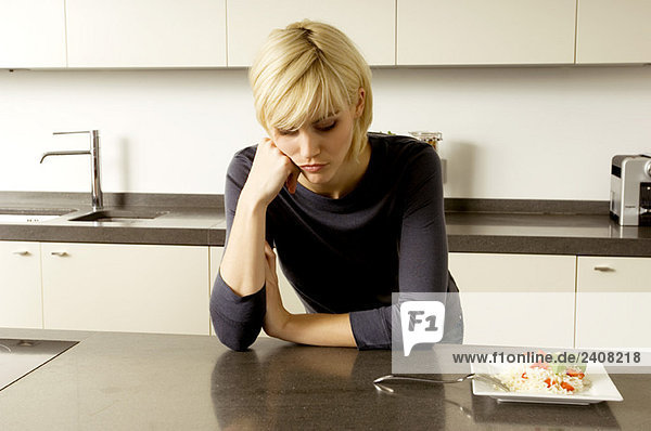 Young woman leaning against a kitchen counter and thinking
