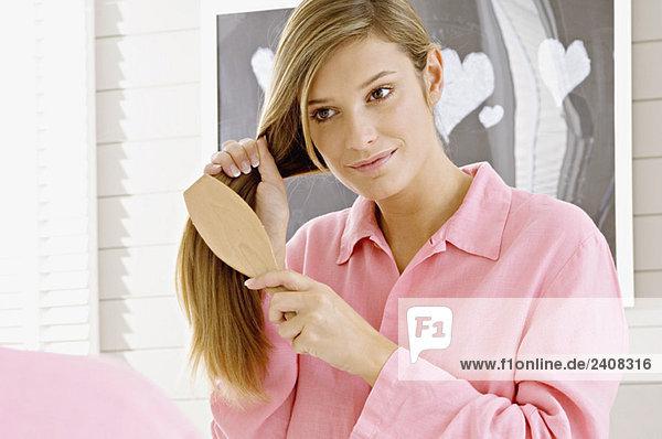 Spiegelung einer jungen Frau  die ihr Haar bürstet