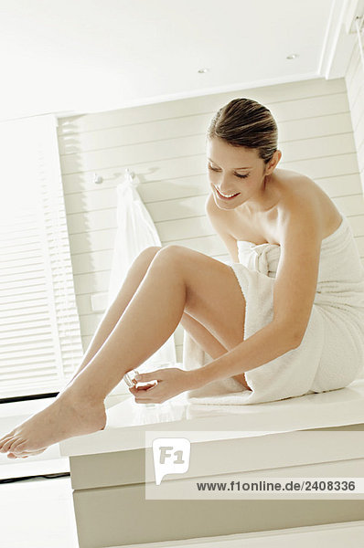 Junge Frau mit Eiswürfel am Bein