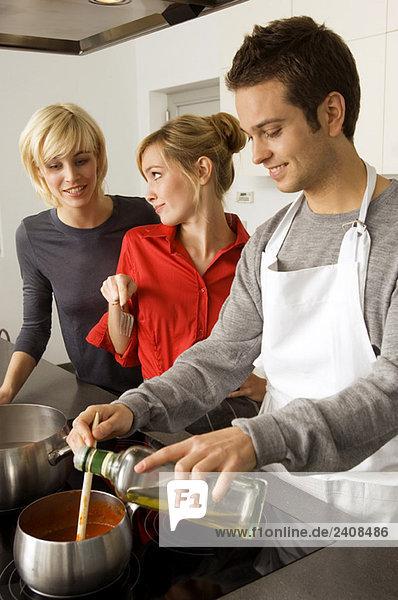 Zwei junge Frauen und ein junger Mann bei der Zubereitung des Essens in der Küche