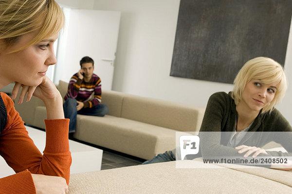 Zwei junge Frauen sehen sich an  ein junger Mann sitzt im Hintergrund.