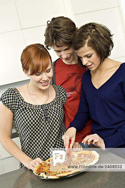 Junge Frau steht mit ihren Freunden und schneidet eine Pizza mit einem Pizzaschneider.