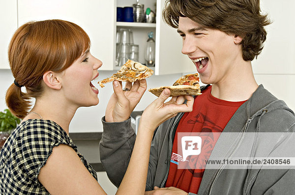 Seitenprofil einer jungen Frau und eines Teenagers  die sich gegenseitig Pizzascheiben füttern.