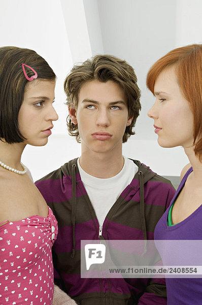 Nahaufnahme eines Teenagers  der mit zwei jungen Frauen steht.