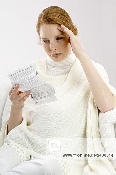 Nahaufnahme einer schwangeren jungen Frau beim Lesen eines Arztberichtes