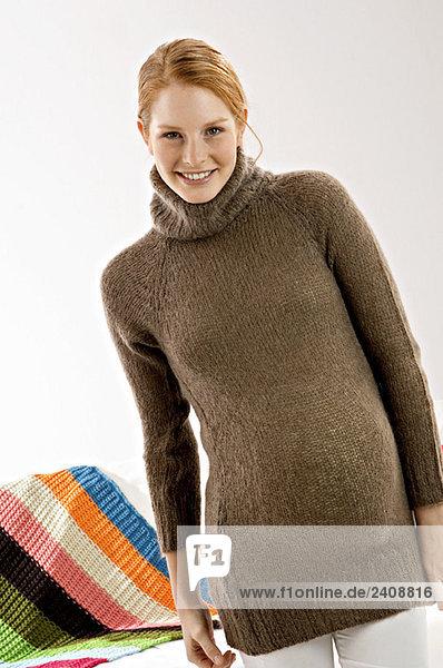 Porträt einer schwangeren jungen Frau stehend und lächelnd