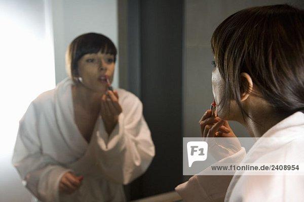 eine Frau  die Lipgloss in einem Spiegel aufträgt.