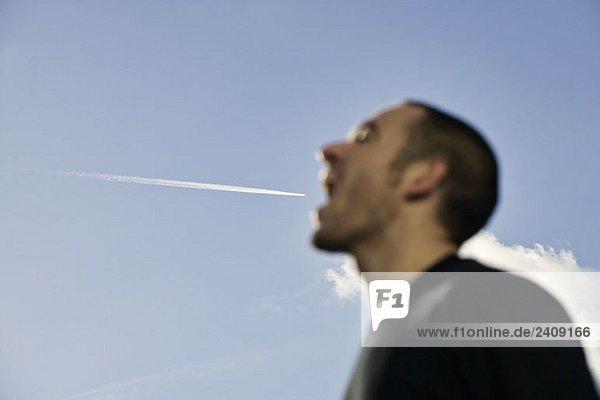 Ein Flugzeug  das in den Mund eines Mannes fliegt. Ein Flugzeug, das in den Mund eines Mannes fliegt.