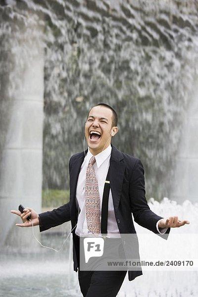 Ein Geschäftsmann  der einem MP3-Player zuhört und singt.