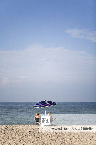 Zwei Leute sitzen am Strand und schauen aufs Meer.