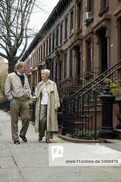 Ein älteres Paar  das auf dem Bürgersteig der Stadt spazieren geht.