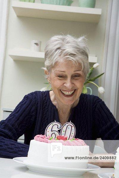 Eine ältere Frau  die auf einen Geburtstagskuchen herabblickt.