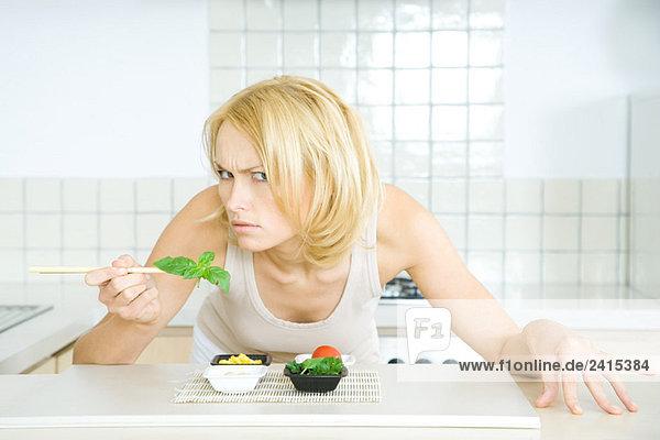 Frau lehnt sich über das Essen  schaut bedrohlich in die Kamera