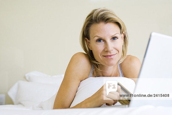 Woman lying on bed  using credit card and laptop  smiling at camera