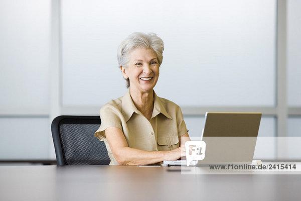 Seniorin am Schreibtisch sitzend  mit Laptop  lachend
