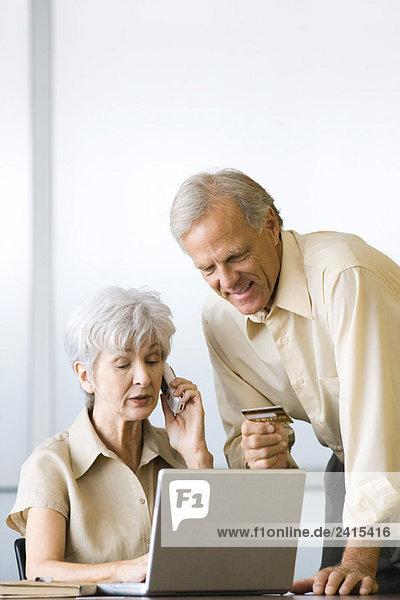 Reife Paare beim Kreditkartenkauf mit Laptop und Handy