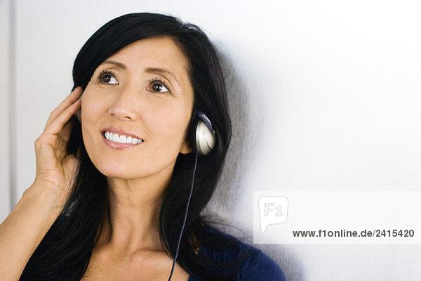 Frau hört Kopfhörer  lächelt