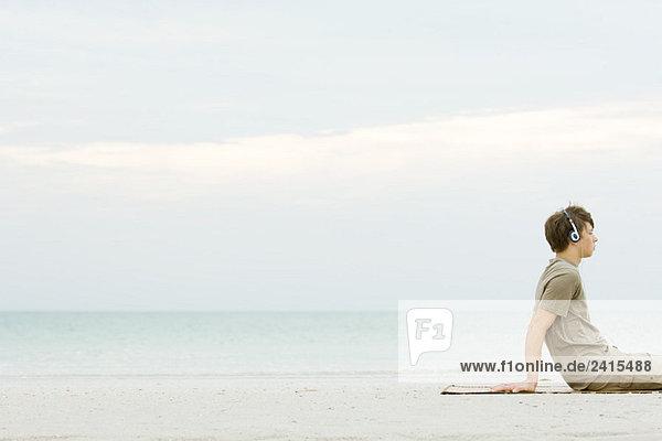 Teen boy sitting on beach listening to headphones  cropped