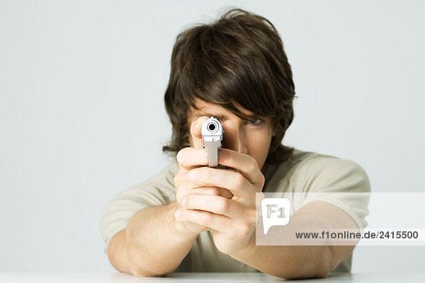 Young man aiming gun at camera
