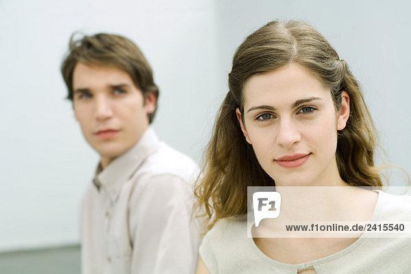 Frau lächelt in die Kamera  Mann dahinter  Frau anschauen