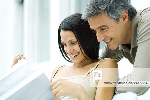 Frau öffnet Geschenktüte  Mann schaut über ihre Schulter  beide lächelnd