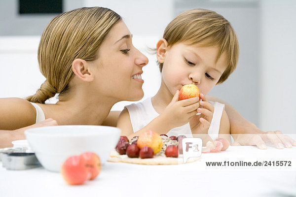 Mother and son preparing food together  boy looking at plum