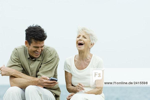 Seniorin und erwachsener Sohn sitzen Seite an Seite im Freien  lachend  Mann hält das Handy.