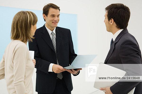 Geschäftspartner stehen zusammen  diskutieren  eine Holdingmappe