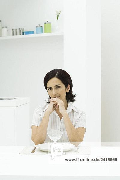 Frau sitzt am Esstisch  die Hände vor dem Mund gefasst  schaut in die Kamera.
