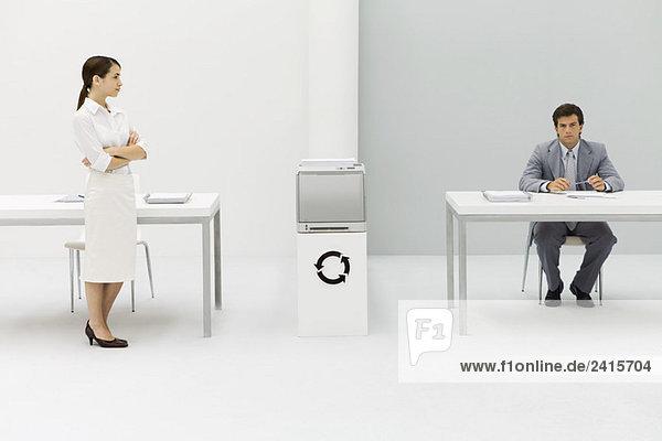 Zwei Profis im Büro  Frau mit gefalteten Armen  Mann mit Blick auf die Kamera  kreisförmiges Pfeilsymbol dazwischen