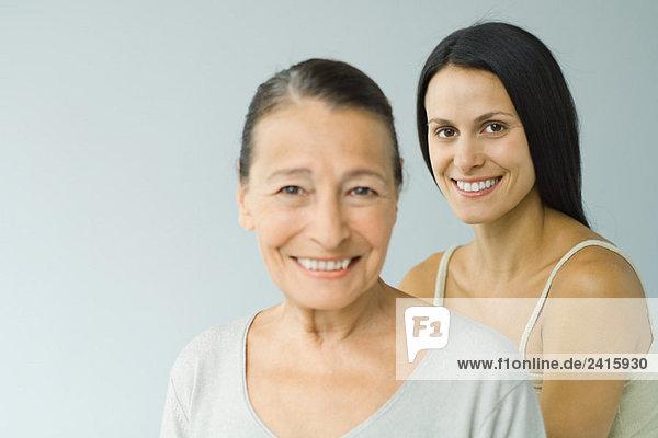 Frau steht hinter Seniorin  beide lächelnd vor der Kamera  Porträt