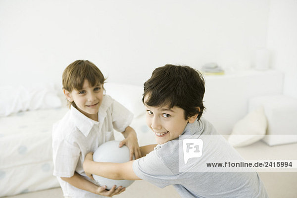 Two boys playing with ball  smiling at camera