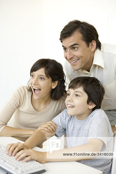 Little boy playing computer video game while his parents watch  all smiling
