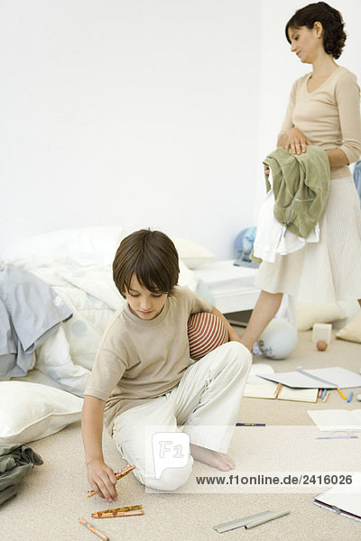 Mother helping boy clean messy room