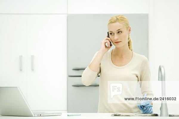Junge Frau steht in der Küche  hält Gummihandschuhe  benutzt Handy