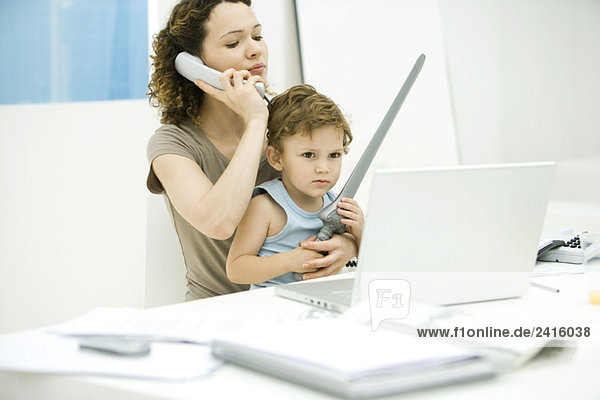 Junge Mutter sitzt am Schreibtisch  während der Sohn auf dem Schoß sitzt und das Schwert hält.