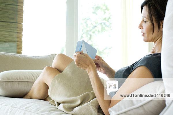 Frau sitzt auf Sofa  Entfernen von Brief aus Umschlag