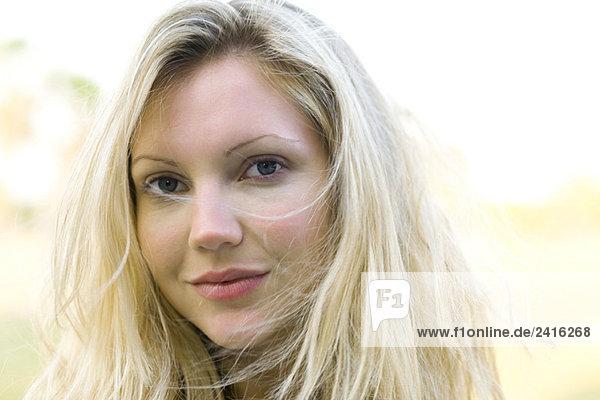 Blonde Frau mit zerzausten Haaren Lächeln in die Kamera
