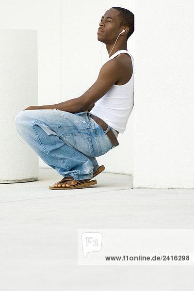 Teen boy crouching  listening to earphones  side view