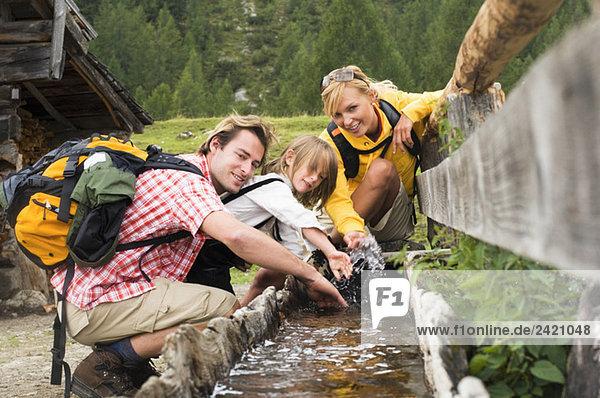 Österreich  Salzburger Land  Paar mit Sohn (8-9) am Trog