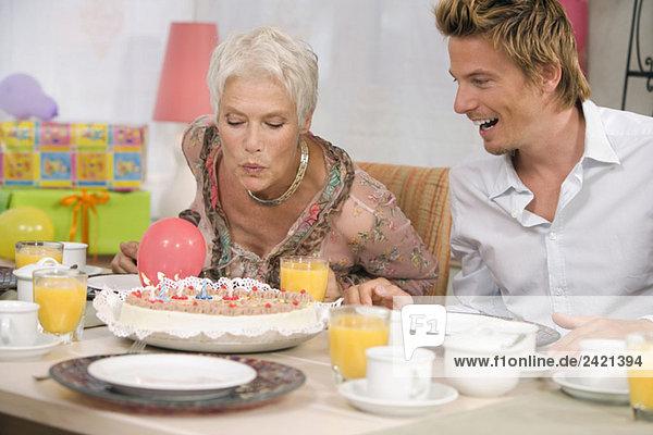 Frau bläst Kerze auf Torte  Portrait
