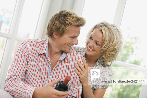 Young couple holding wine bottle  smiling  portrait
