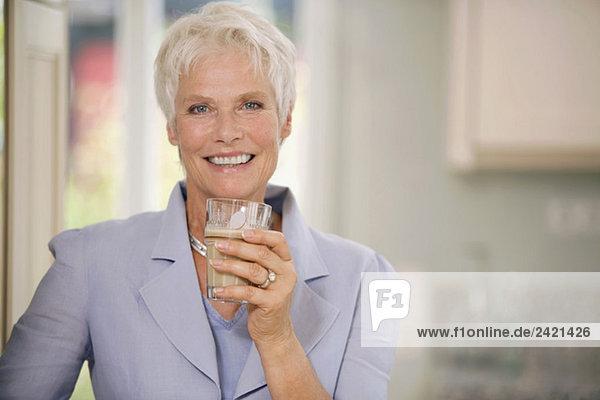 Frau hält Trinkglas  lächelnd  Portrait