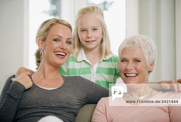 Mädchen (8-9) mit Mutter und Großmutter im Wohnzimmer  lächelnd  Porträt