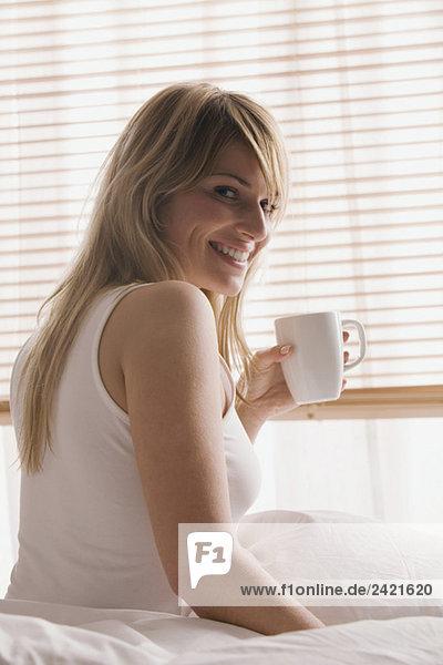 Blonde Frau mit einer Tasse Kaffee  lächelnd  Portrait