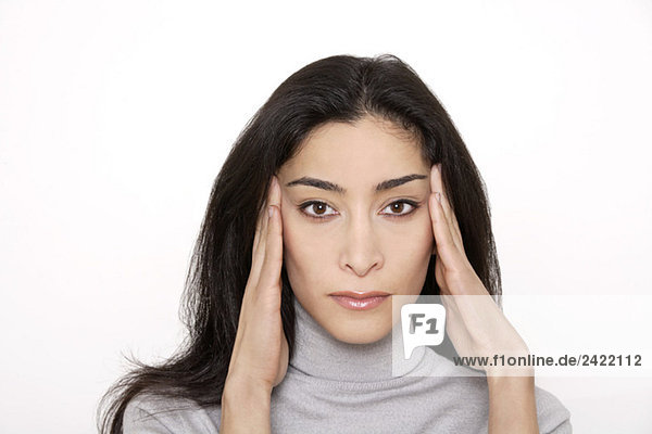 Junge Frau hält Kopf in Händen  Portrait