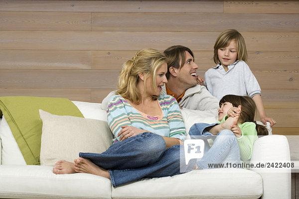 Familie auf Sofa sitzend  lächelnd  Portrait